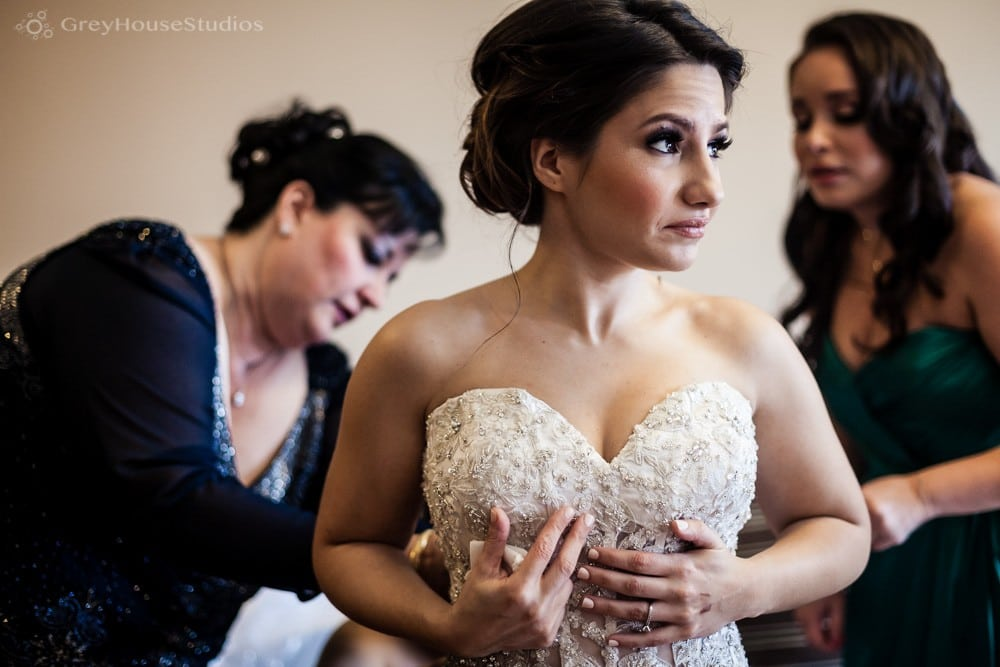 long island wedding photos bride putting on dress with mom