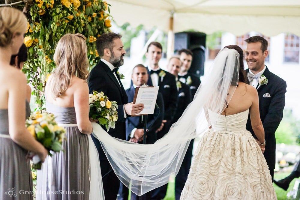 winvian wedding ceremony photos bridesmaid holds bride's veil